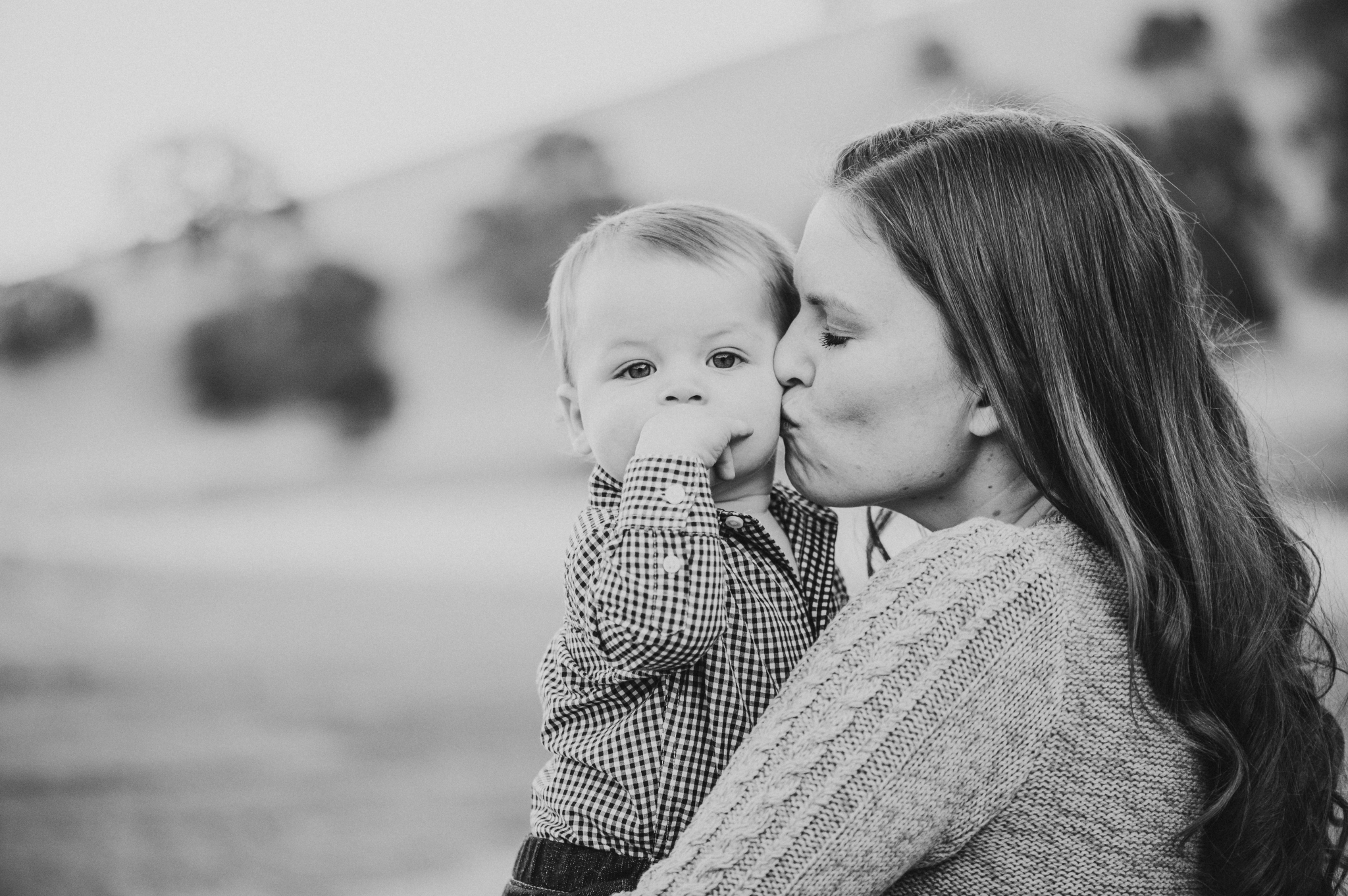 photograph of mother kissing child